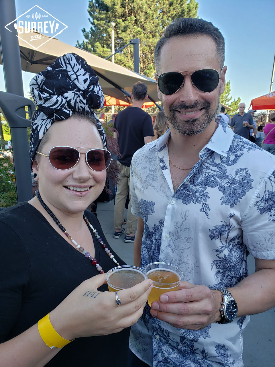 Surrey Eats writers Erin and Matt cheers while holding beer and wearing sunglasses