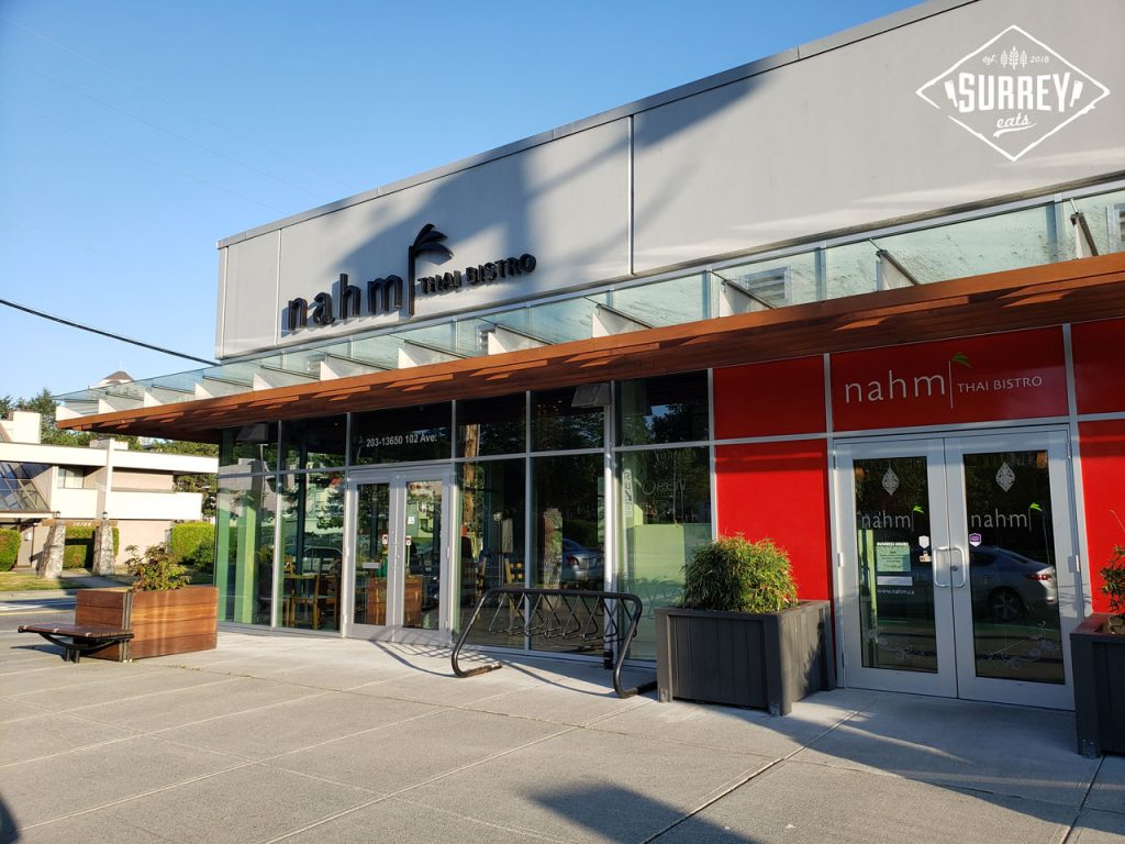 The res and grey exterior of Nahm Thai Bistro in Surrey on a bright sunny day.