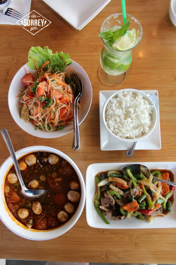 A view of the entire dinner from Nahm Thai. pictured from clockwise from top left: Papaya Salad, Gin Soda, Large Rice, Pad Grapau Beef, Tom Yum Chicken