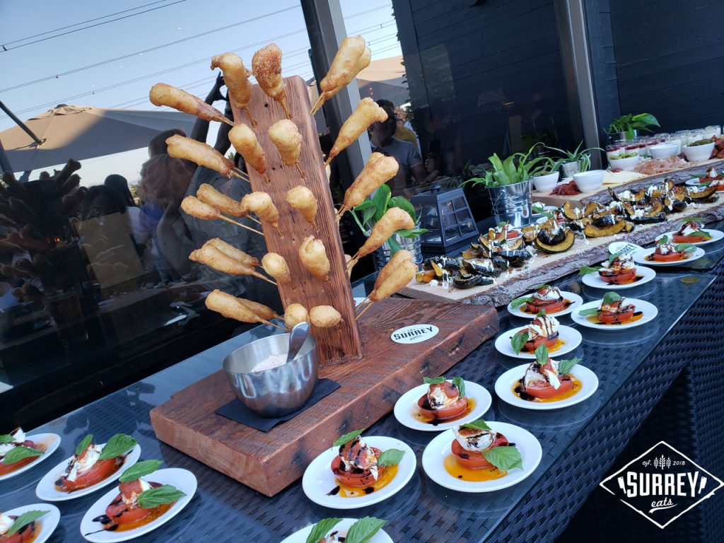 A wooden stand is studded with Prawn pogos and surrounded by caprese salads and roasted acorn squash
