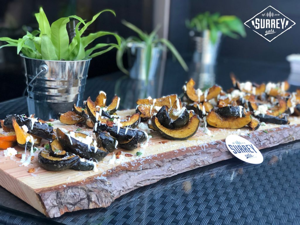 Roasted Acorn Squash served on a wooden plank with a Surrey Eats sticker propped up on it