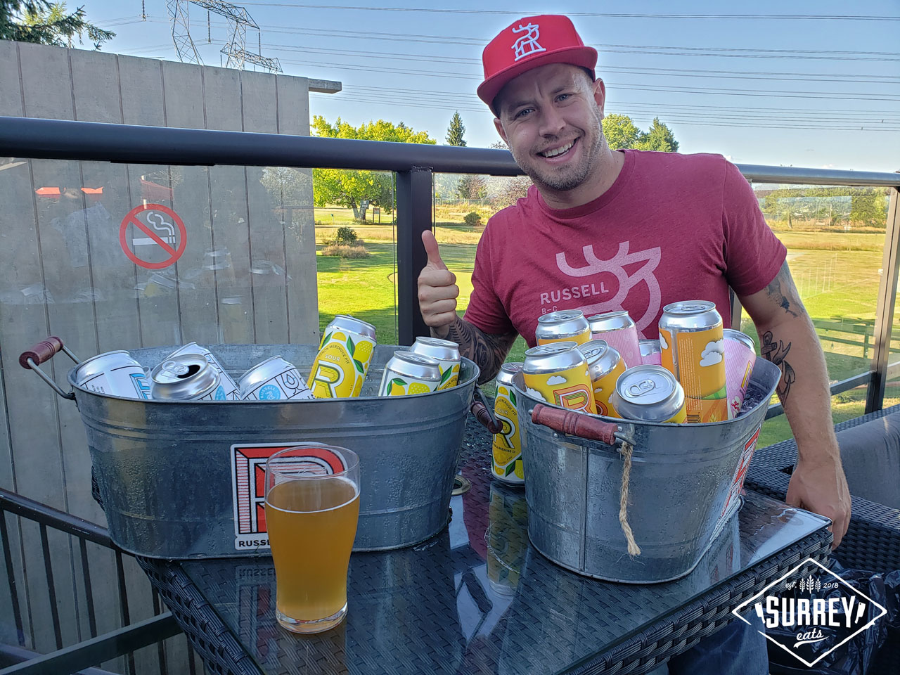 Walker from Russell Brewing gives the thumbs up at a table with two icebins of beer