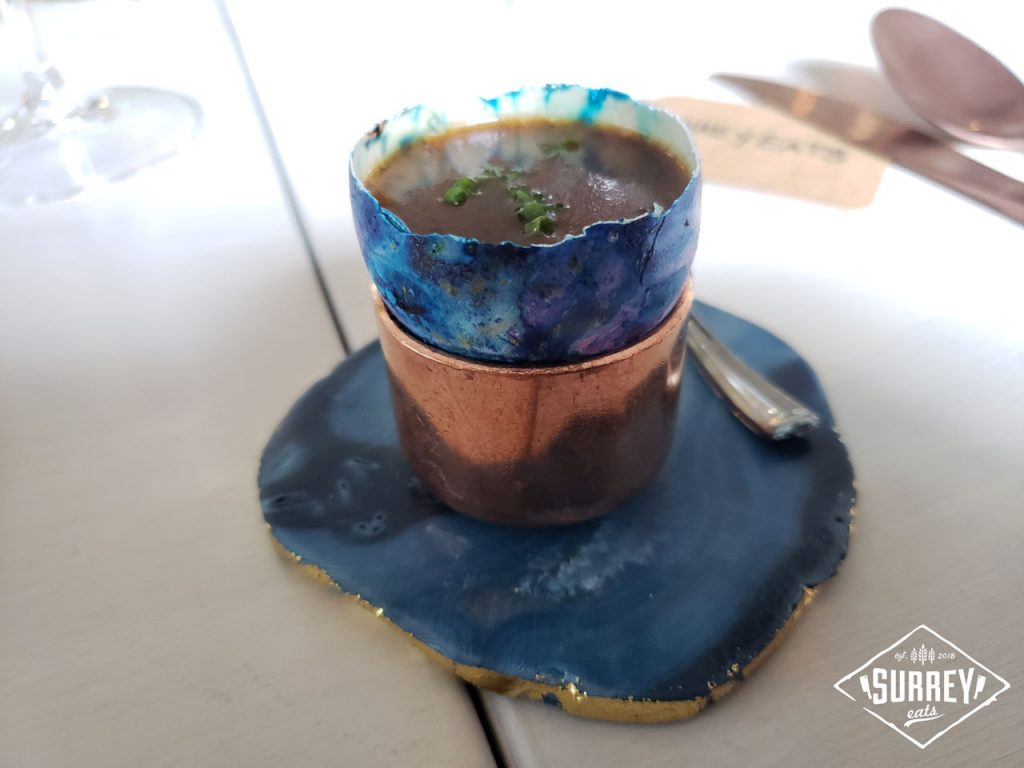 Truffle custard served in a painted  purple and blue eggshell on a matching coaster