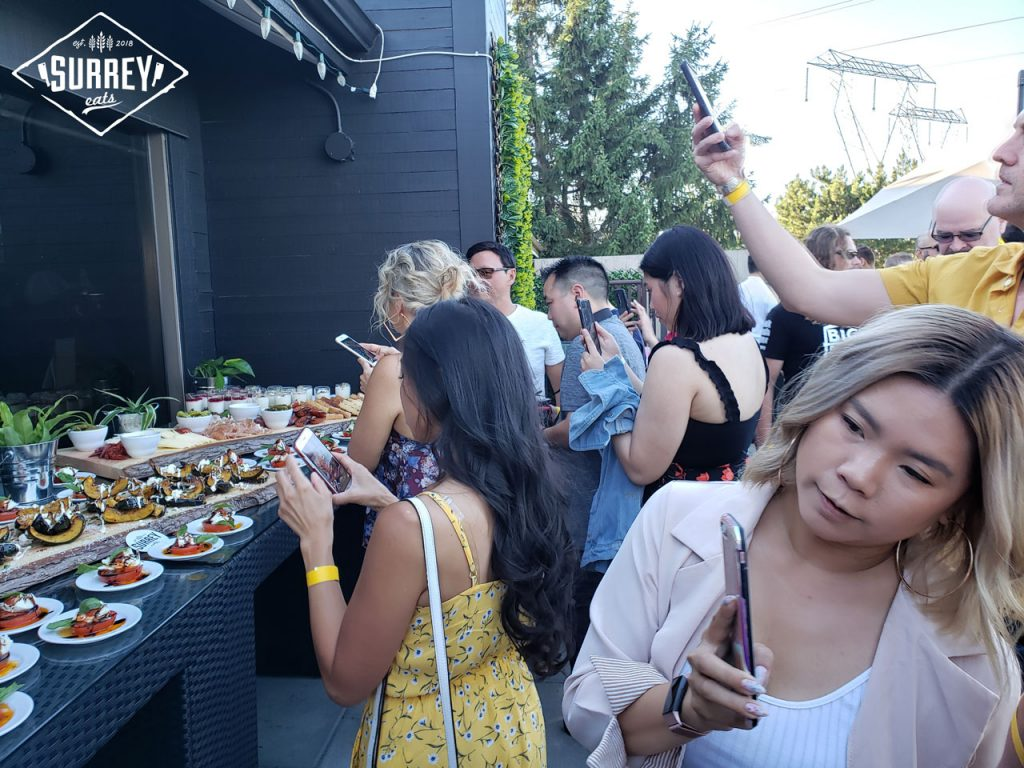 Partygoers line a food spread to take photos at Surrey Eats Summer Social