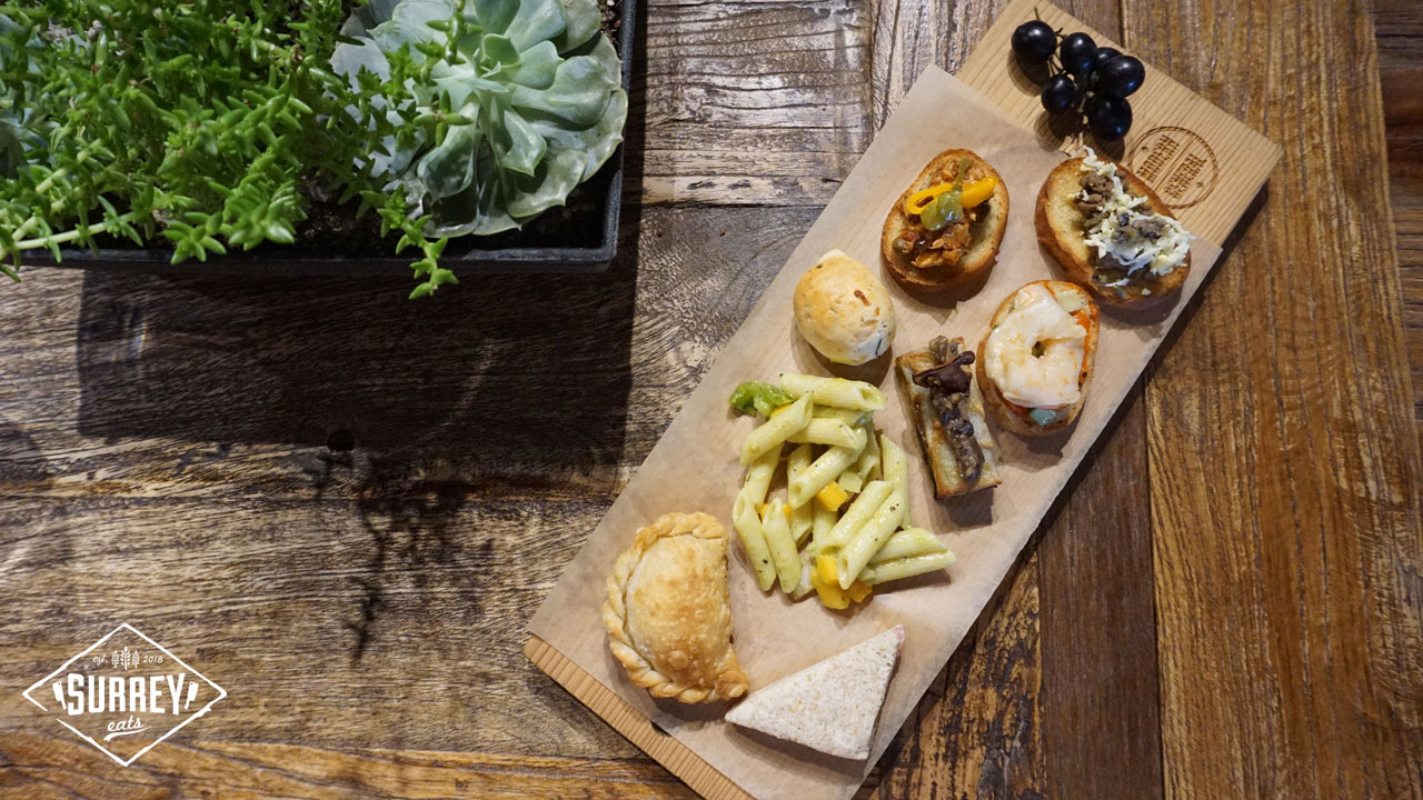 A board of tapas is positioned diagonally beside a succulent plant