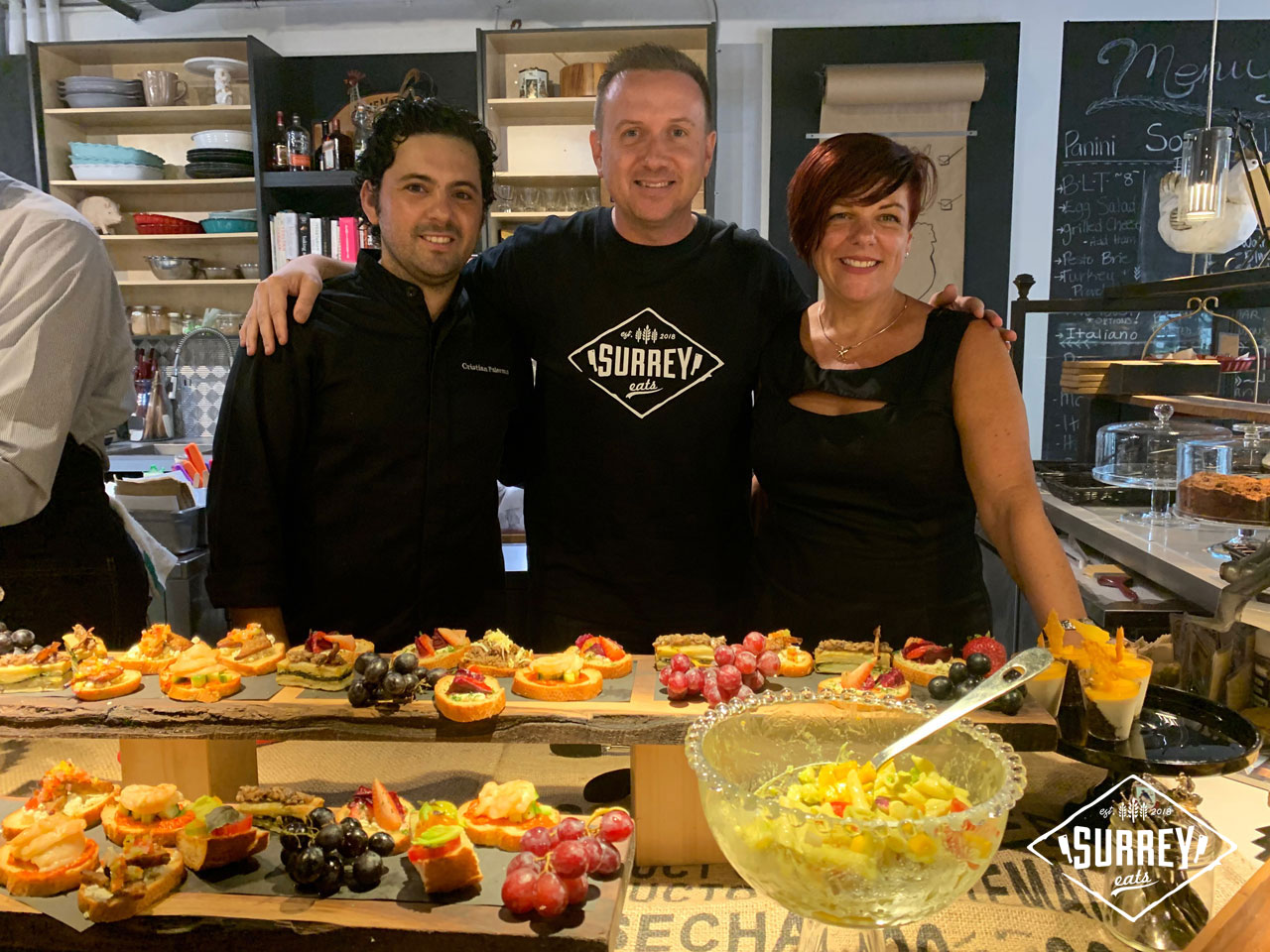 Craig from Surrey Eats poses for a photo with Chef Cristian Palermo and Modern General owner Laura Virginillo with a spread of tapas in front of them