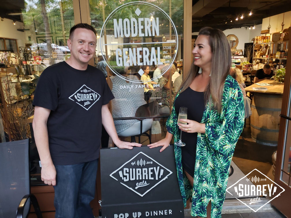 "Craig from Surrey Eats poses with Rachel in front of the Modern General with a sign that reads ""Surrey Eats Pop Up Dinner"""