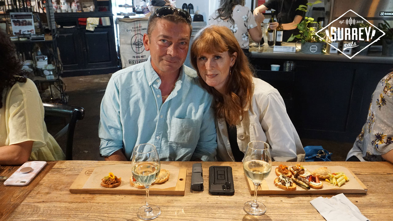 Julie and husband seated at a wooden table with glasses of wine and tapas boards