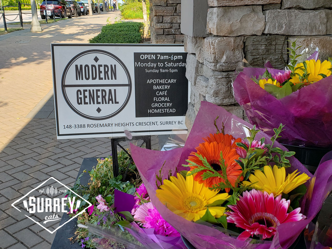 "A sign reads ""Modern General"" in front of some flower bouquets"