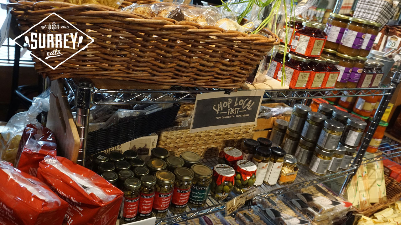 "A sign reads ""Shop local first"" on a shelf of olives and other goods at the Modern General Store Inc."