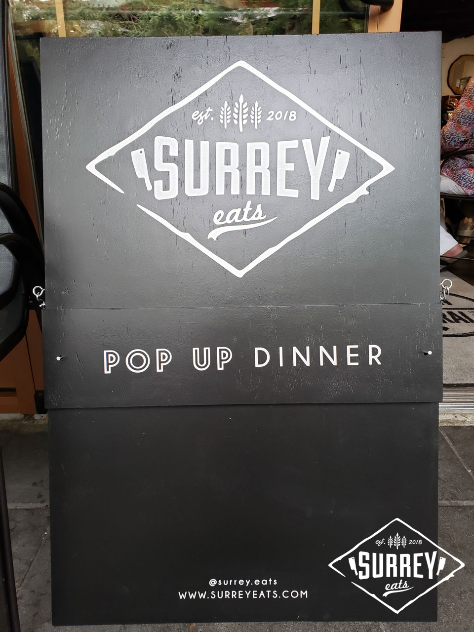 A sandwich board sign reads Surrey Eats Pop Up Dinner