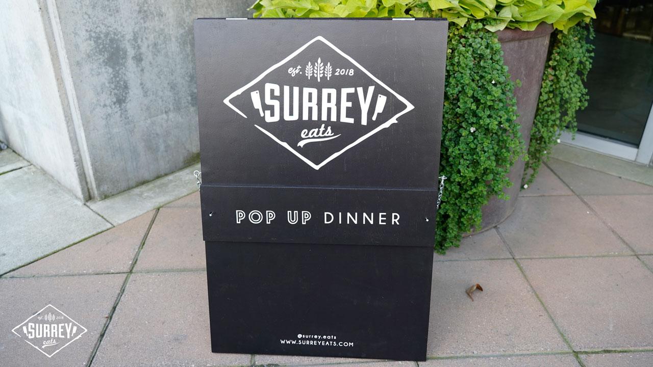 """A black sandwich board reads """"Surrey Eats Pop Up Dinner"""""""