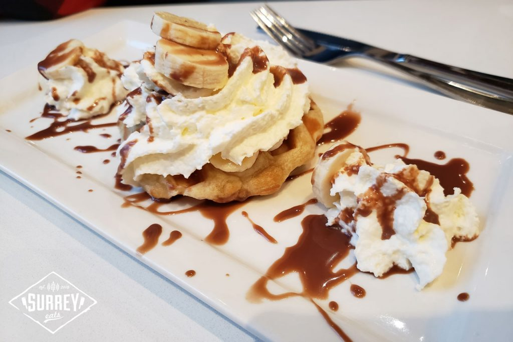 Belgian Monkey Waffle; a waffle topped with whipped cream and bananas with drizzled caramel sauce