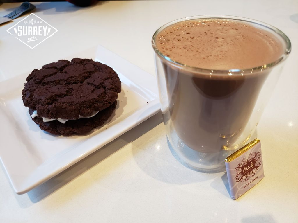 A glass of Drinking Chocolate with an Oreo whoopie cushion dessert and a small Extra Dark Mink Chocolates bar wrapped in gold foil