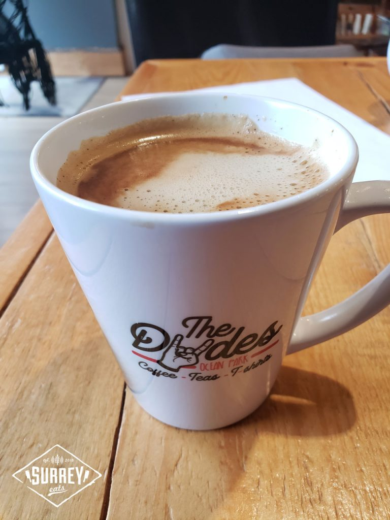 A mug of coffee emblazoned with The Dudes Ocean Park Coffee-Teas-T-shirts