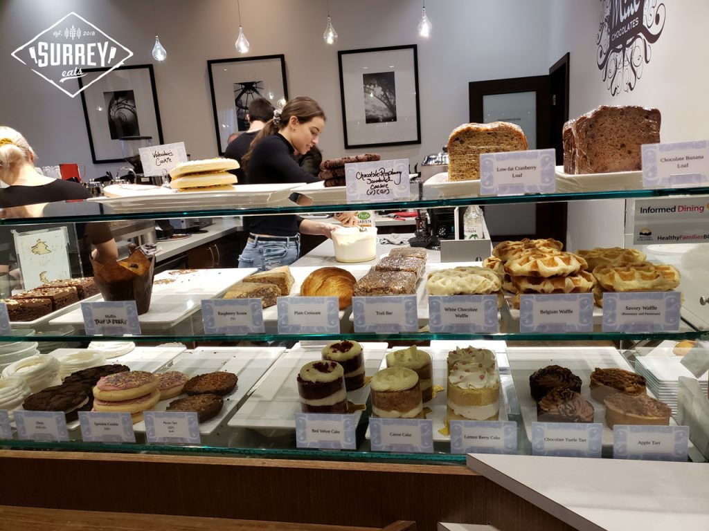 A selection of baked goods in a glass display at Mink Chocolates' Surrey location