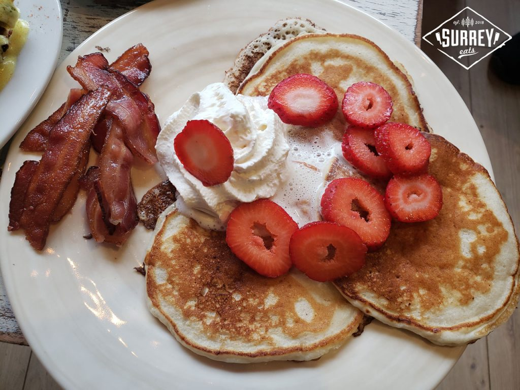 Three pancakes topped with sliced strawberries and whipped cream with a side of bacon