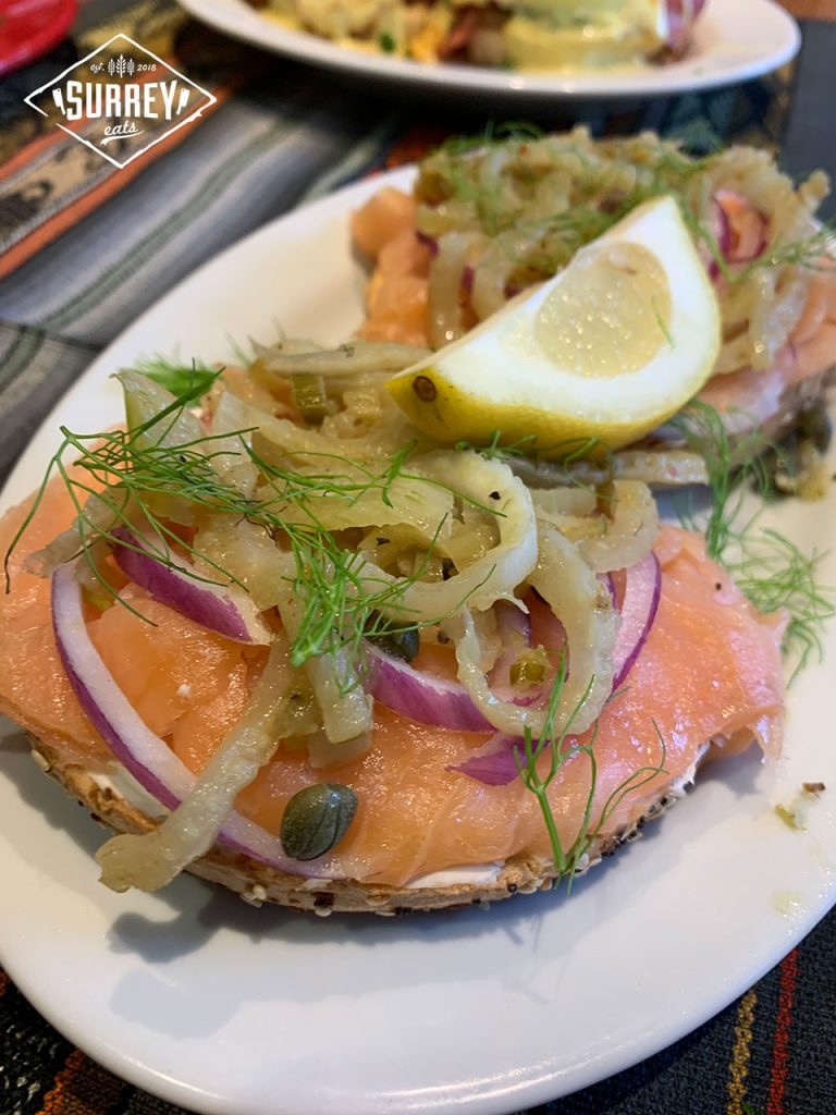 A Smoked Salmon bagel topped with purple onion, capers, dill, fennel and a wedge of lemon