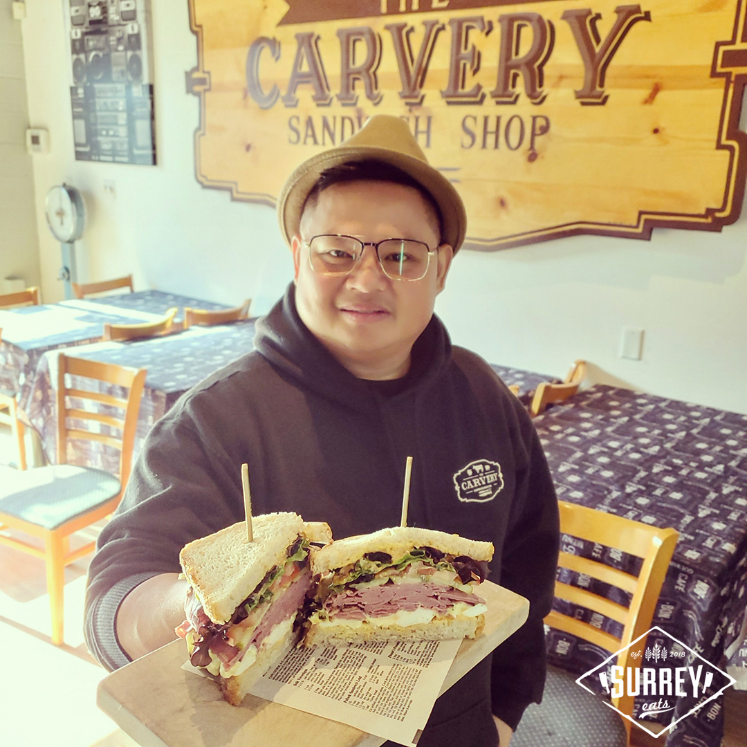 Bryan holds up a sandwich from The Carvery Sandwich Shop