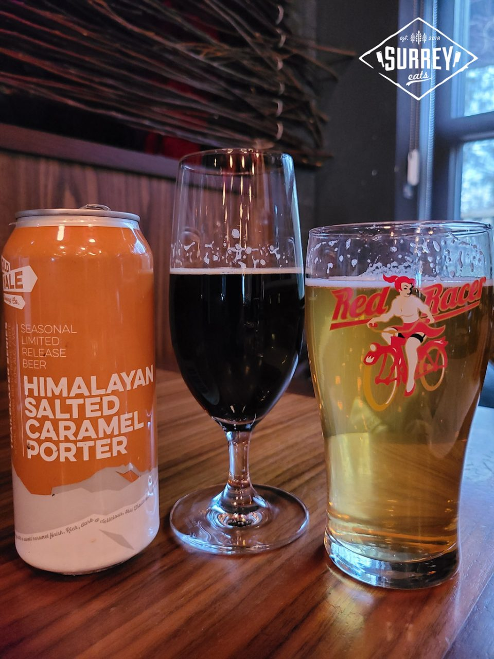 A can of Himalayan Salted Caramel Porter next to a glass of the dark beer and a glass of Red Racer lager