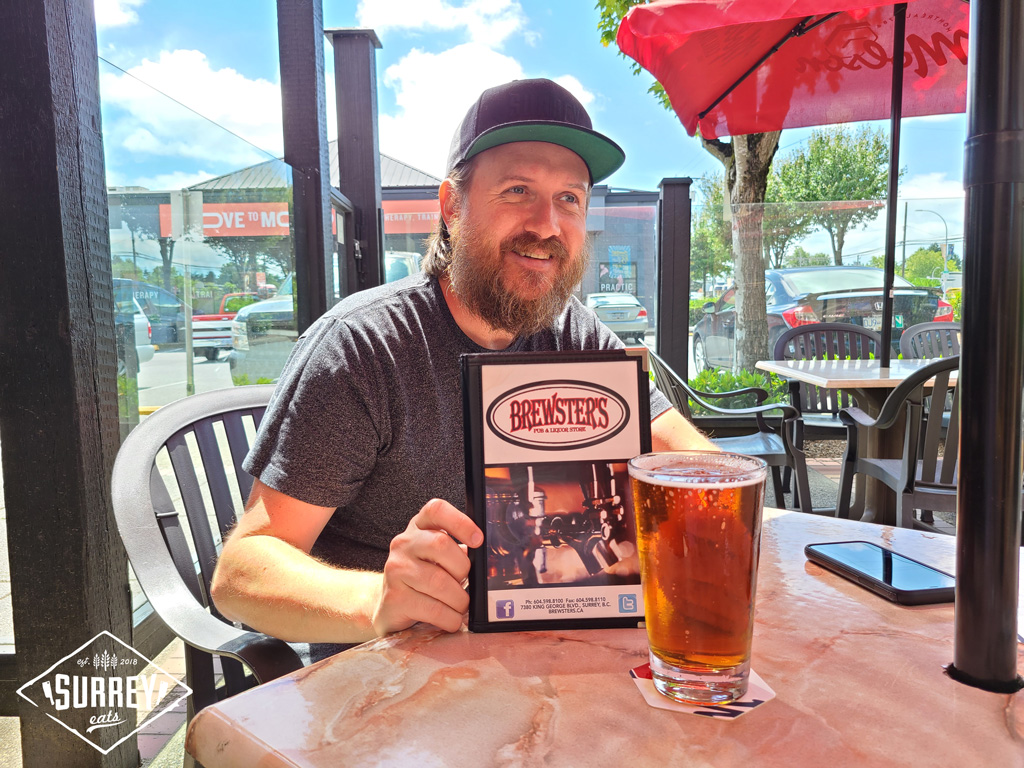 Craig from Surrey Eats holds a menu from Brewster's Pub