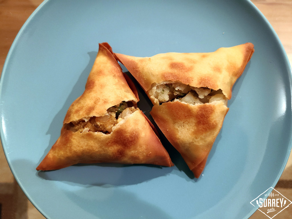 Two samosas on a round blue plate. Both are broken open to show some potato within.