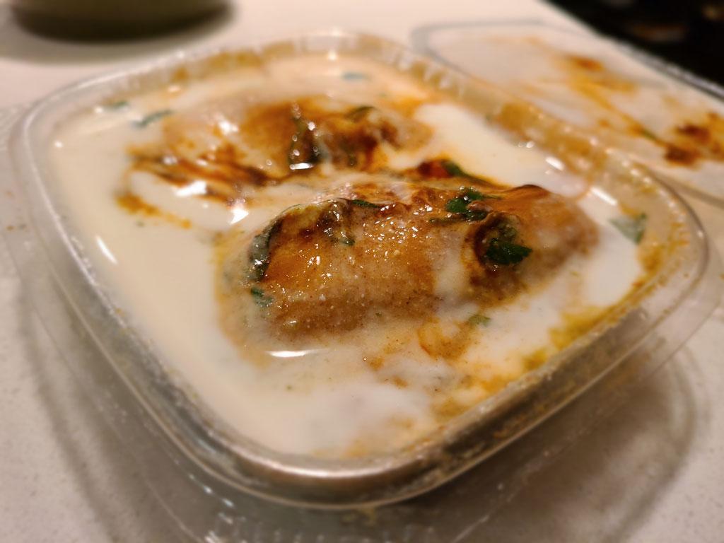 Two Dahi gujjias, a lentil dumpling in yogurt and tamarind sauce.