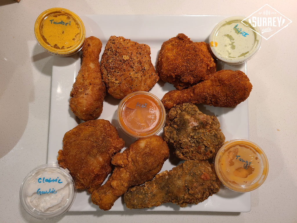 8 pieces of Major Joy Chicken including Lemon Pepper, Tandoori, Major Hot, and Fresh Chilli Mint. Plus Classic Garlic, Tandoori, Mint, Tangy, and Hot sauces all arranged on a plate