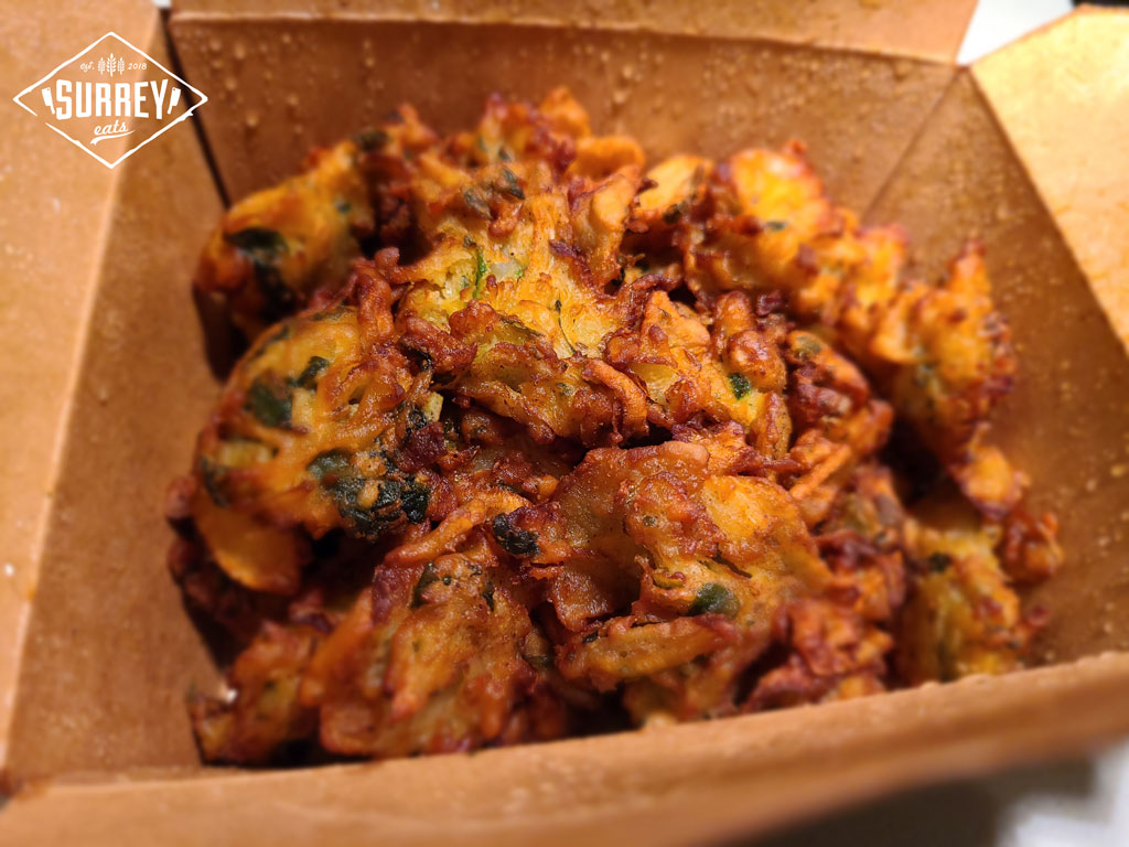 Close up of mixed vegetable pakora in a take-out box.