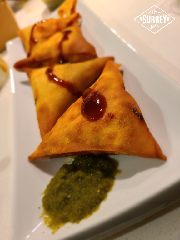 A row of four samosas from Samosa House on a rectangular plate drizzled with tamarind sauce and a spot of green mint chutney on the side.