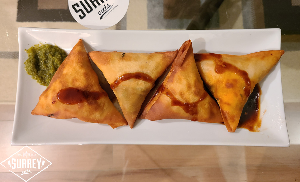 A plate of four samosas drizzled with tamarind chutney with some spicy mint chutney on the side. Surrey Eats stickers are visible above the plate.