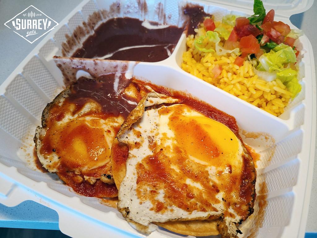 Huevos Rancheros with beans, crema, rice and salad.
