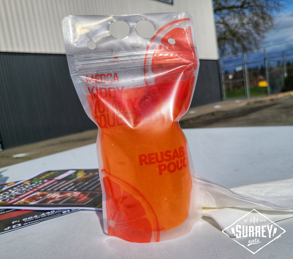 A reusable pouch bag of Island Strawberry Lemonade rests on a table with some flyers advertising Tommies Jerk's grand opening