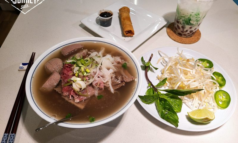 a combo meal from pho an nam in Surrey, including pho dac biet, a spring roll, and three colour dessert with some veggies on the side.