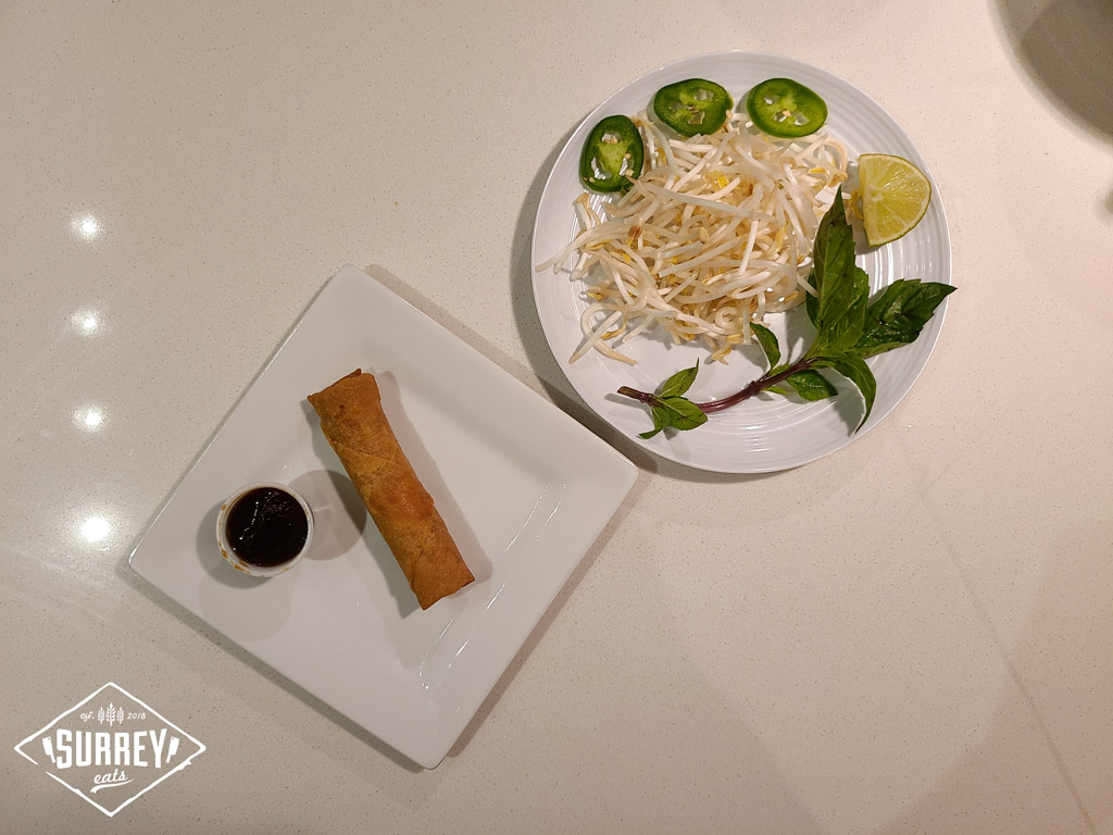 A spring roll with hoisin sauce and a plate of pho veggie toppings