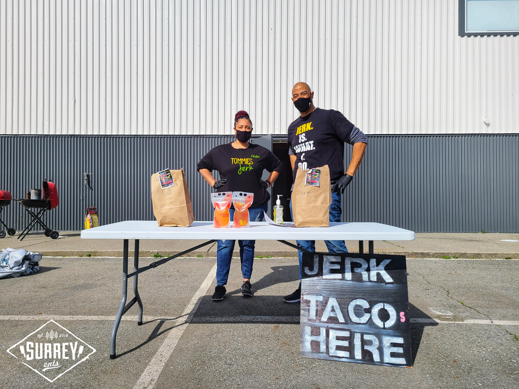 """The owner and a staff member of Tommies Jerk pose at a table with a sign that says """"Jerk Tacos Here""""."""