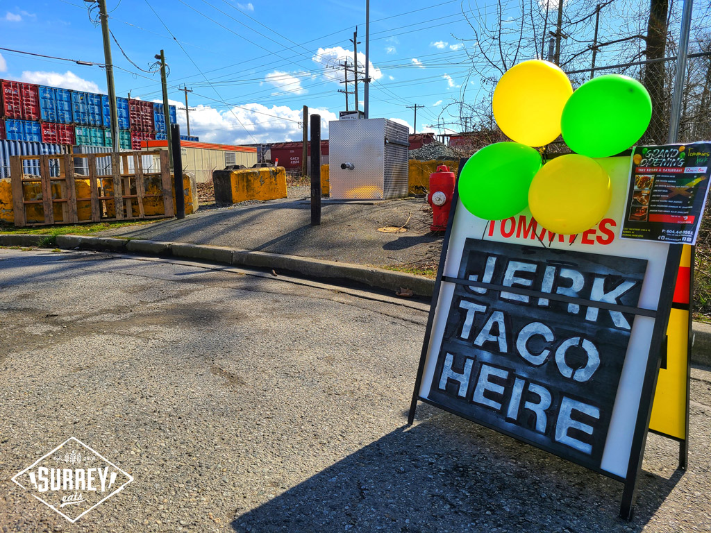 "A sign with green and yellow balloons advertises ""Tommies Jerk Taco Here"" with a grand opening flyer attached to it. An industrial area with shipping containers is in the background."