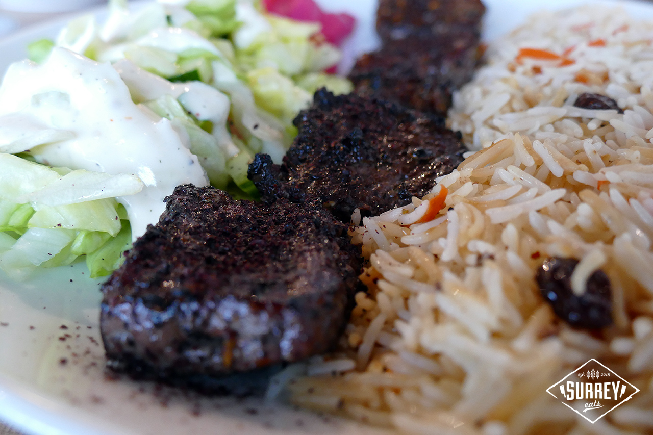 Closeup of beef dish with rice and salad