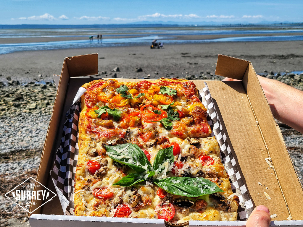 Opening a box of Roman style pizza from Natalino's Pizza on the beach at Crescent Beach