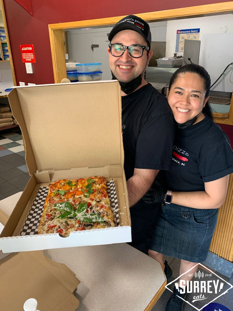 The owners and operators of Natalino's Pizza posing with a fresh-made al taglio pizza