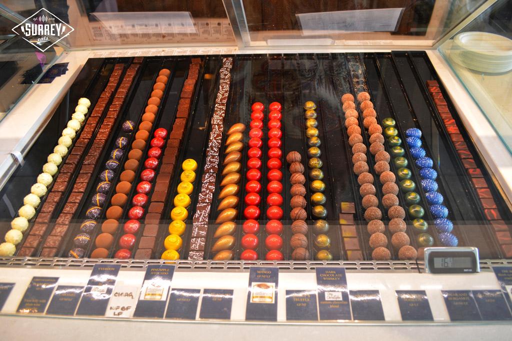 An array of swiss chocolates under glass