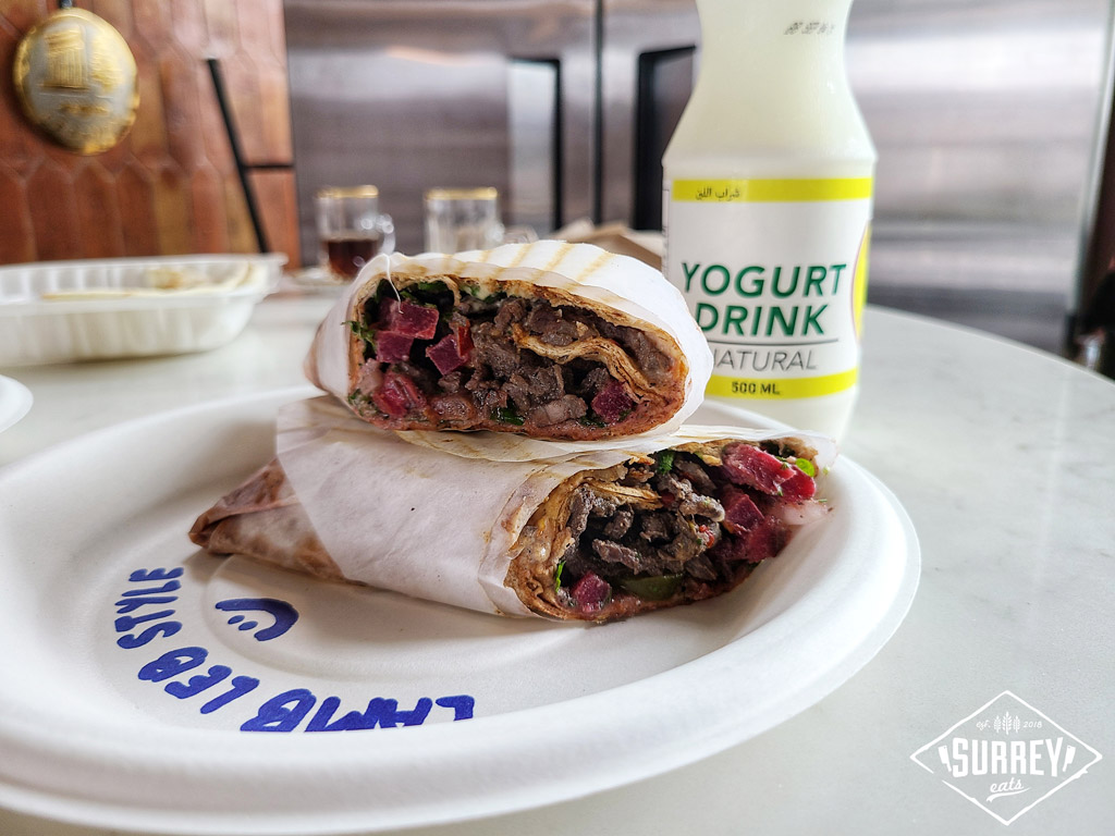 Lamb Lebanese style wrapped in tannour bread with a bottled yogurt drink in the background