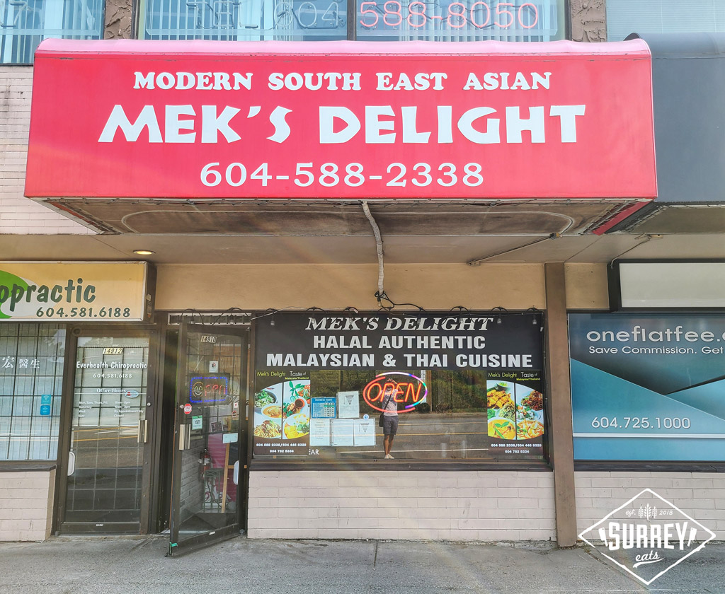"""Mek's Delight restaurant storefront with a red awning that reads """"Mek's Delight Modern Southeast Asian 604-588-2338"""". The window advertises Halal Authentic Malaysian & Thai Cuisine."""