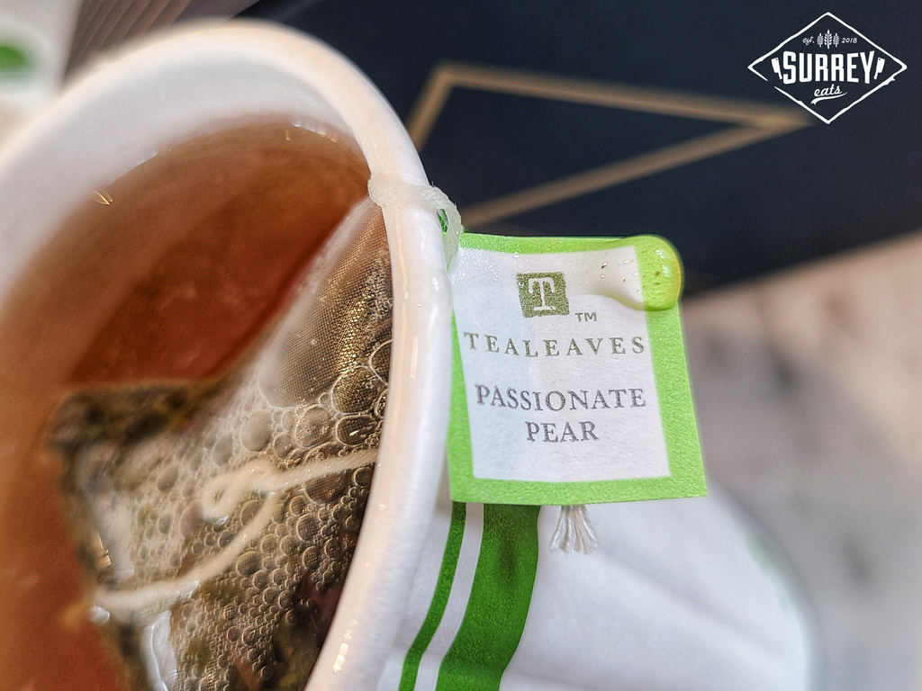 """Close up of a cup of tea shot from an angle with the teabag label in focus which reads """"Tealeaves Passionate Pear"""""""
