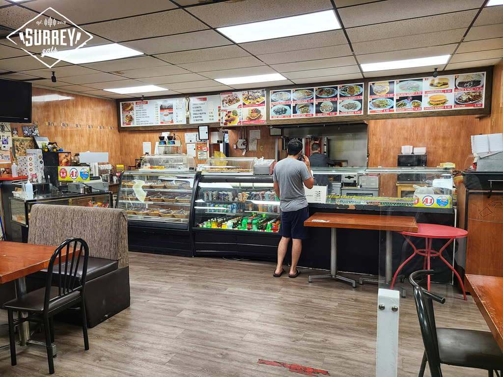 A man stands at the counter on his cellphone with the A1 Coffee & Donair menu in the background