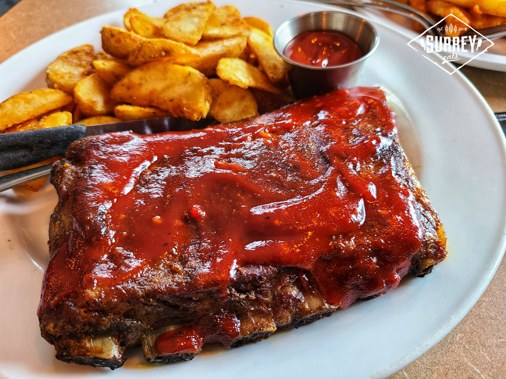 Half-rack of BBQ Pork Ribs with Wedge Fries and a side of ketchup