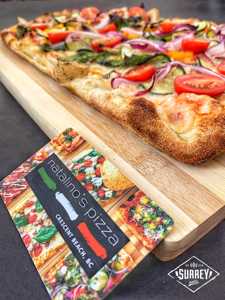 """A business card reading """"Natalino's Pizza Crescent Beach, BC"""" leans against a cutting board with a vegan pizza on it"""